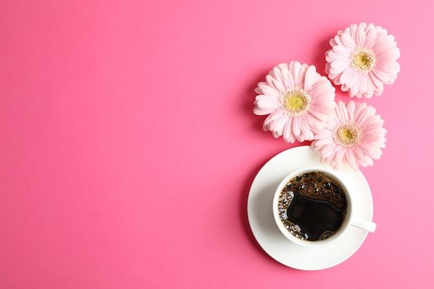 Mooie roze gerbera's en kopje koffie op kleur, bovenaanzicht. ruimte voor tekst