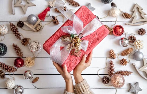 Mooie roze geschenkdoos in handen tegen de achtergrond van details van kerstdecor close-up.