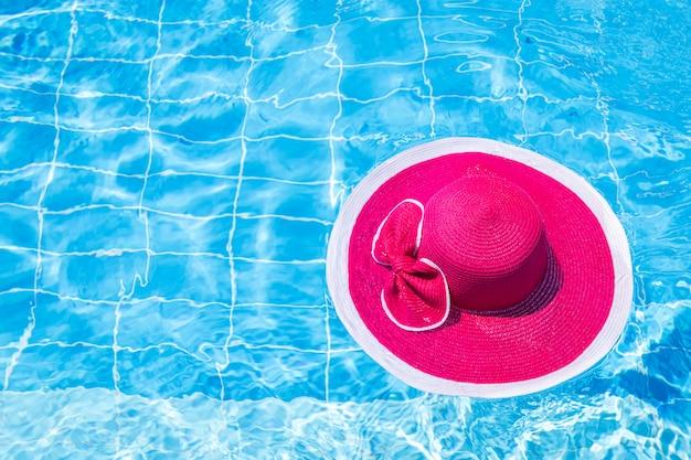 Mooie roze hoed met strik op wateroppervlak in zwembad