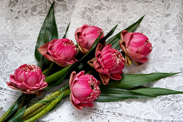 Mooie roze lotusbloem voor biddende boeddha op tafel