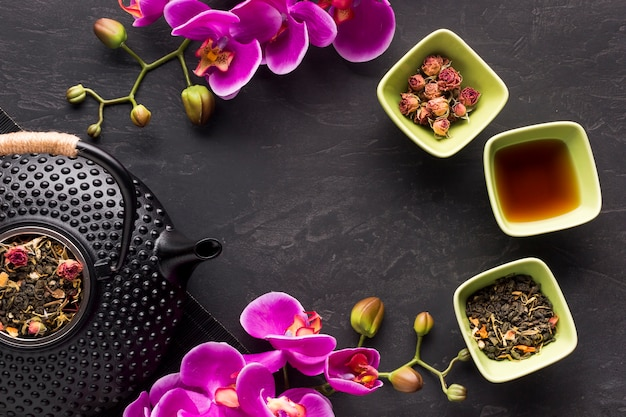 Mooie roze orchideebloem met droog theekruid met modieuze zwarte theepot op zwarte oppervlakte