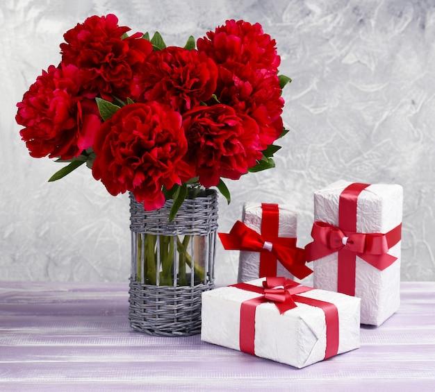 Mooie roze pioenrozen en geschenken op houten tafel