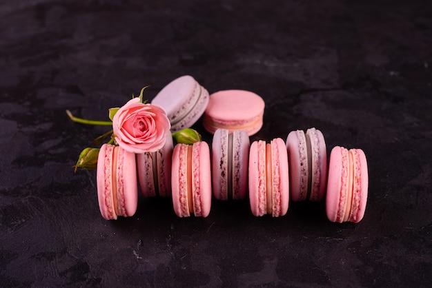Mooie roze smakelijke bitterkoekjes op een concrete achtergrond