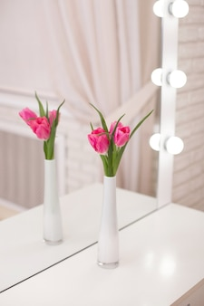 Mooie roze tulpen in vaas op tafel in de schoonheidssalon, lente decor
