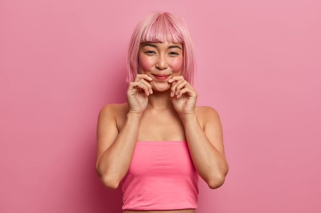 Mooie rozeharige aziatische dame lacht aangenaam, houdt de handen bij de lippen blij om aangenaam nieuws te horen, draagt een roze top staat binnen. monochroom. etnisch meisje met trendy kapsel drukt goede emoties uit