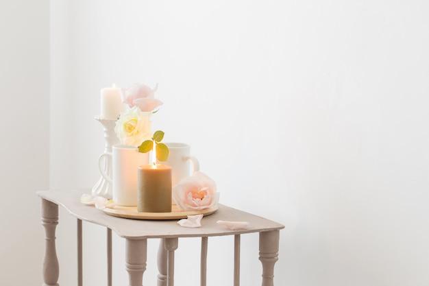 Mooie rozen en brandende kaarsen op witte achtergrond