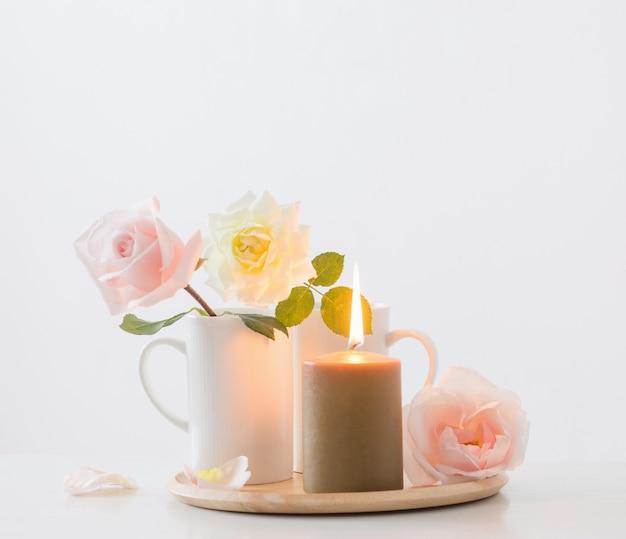 Mooie rozen en brandende kaarsen op witte muur