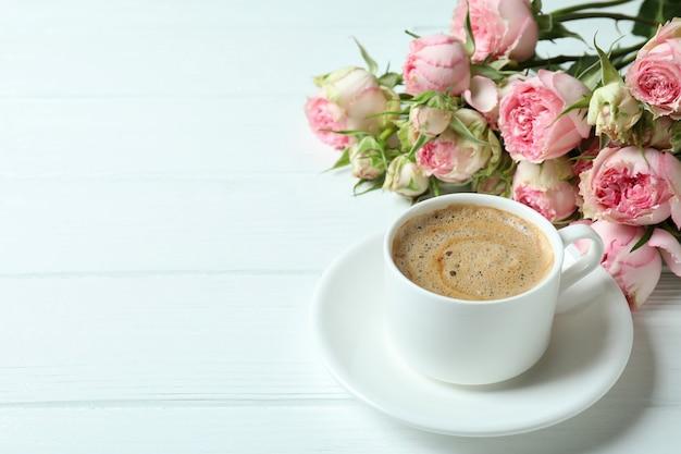 Mooie rozen en kopje koffie op witte houten