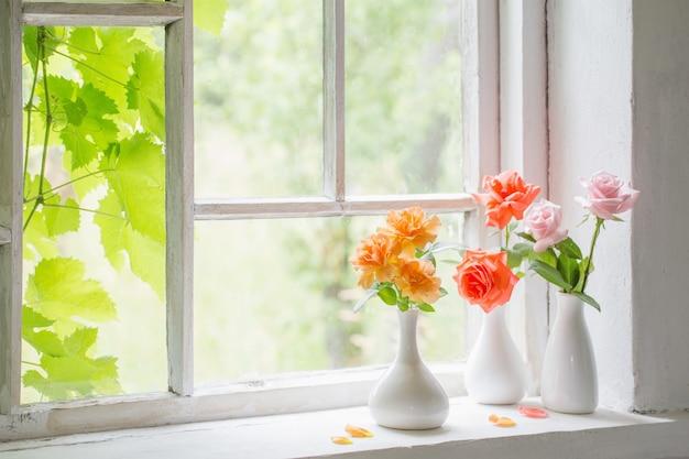 Mooie rozen in vazen op oude houten vensterbank