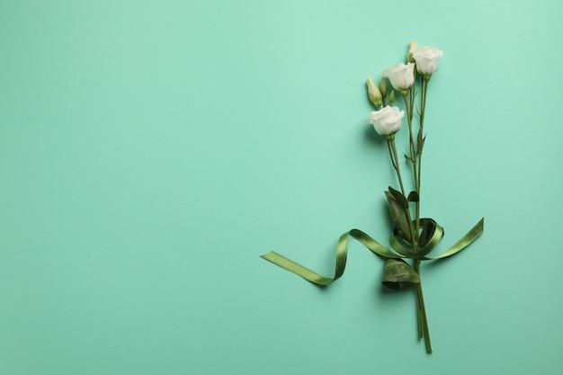 Mooie rozen met groen lint op munt achtergrond