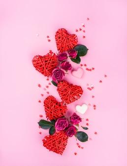 Mooie rozen met harten op een roze achtergrond, inhoud voor valentijnsdag.