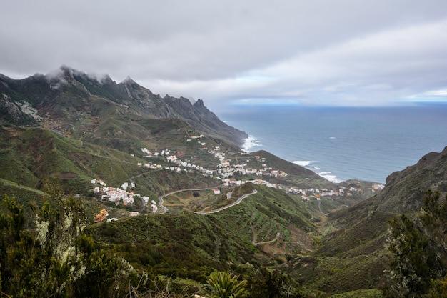 Mooie rustige uitzicht op groene, met gras begroeide steile helling. tenerife. mooi dorp op de hellingen van de berg.