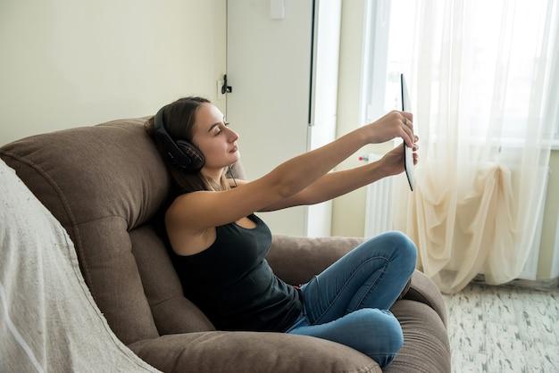 Mooie rustige vrouw die digitale tablet gebruikt terwijl ze op de bank in de woonkamer zit