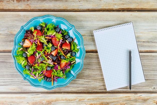Mooie salade met blocnote en pen voor snelle memo