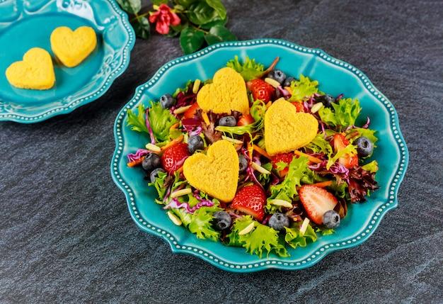 Mooie salade met groenten, bessen en kipnuggets voor valentijnsdag