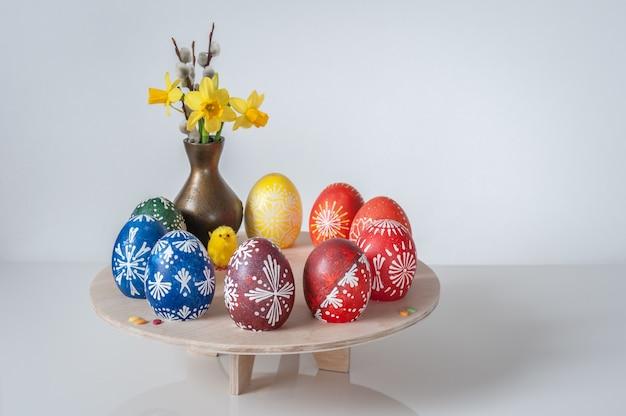 Mooie samenstelling met geschilderde eieren, wilgentakken en boeket van de lentebloemen