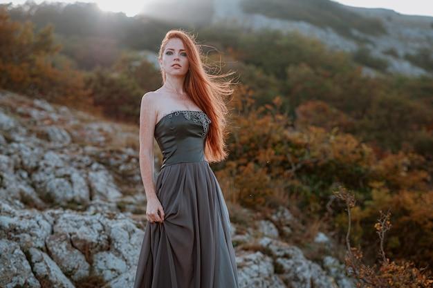 Mooie scandinavische krijger gember vrouw in grijze jurk met metalen ketting