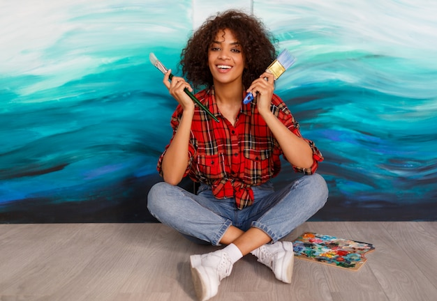Mooie schattige afrikaanse etniciteit student houden borstels en poseren over haar abstracte kunstwerken op canvas.