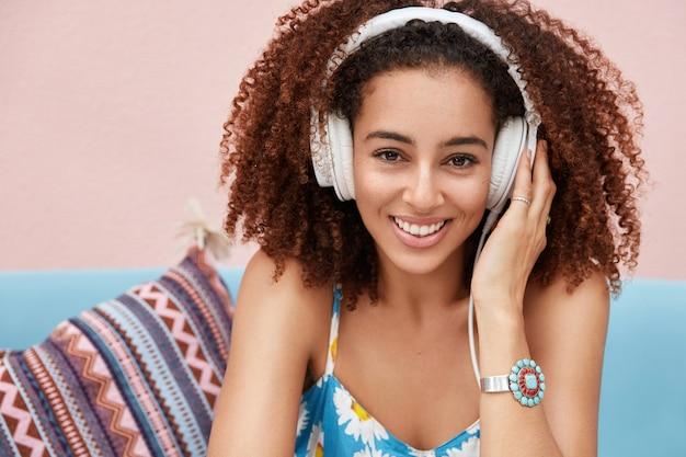 Mooie schattige afro-amerikaanse vrouw luistert radio-uitzending in moderne koptelefoon, in goed humeur