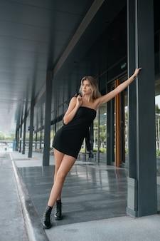 Mooie schattige blonde vrouw die zich voordeed in een zwarte korte jurk in lederen schoenen met een lederen jas op haar schouder