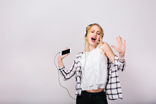 Mooie schattige blonde vrouw geniet van haar leven, zingen en dansen met gesloten ogen. vrolijk slim meisje dat een stijlvolle witte blouse met een zwarte broek draagt.