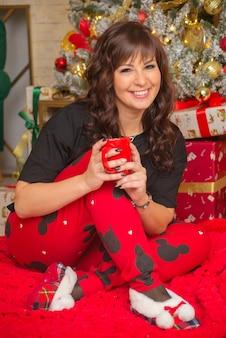 Mooie schattige gelukkige jonge vrouw in kerstmis thuis hete thee drinken