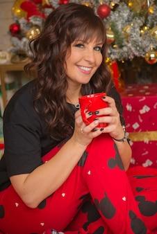 Mooie schattige gelukkige jonge vrouw in kerstmis thuis warme chocolademelk drinken