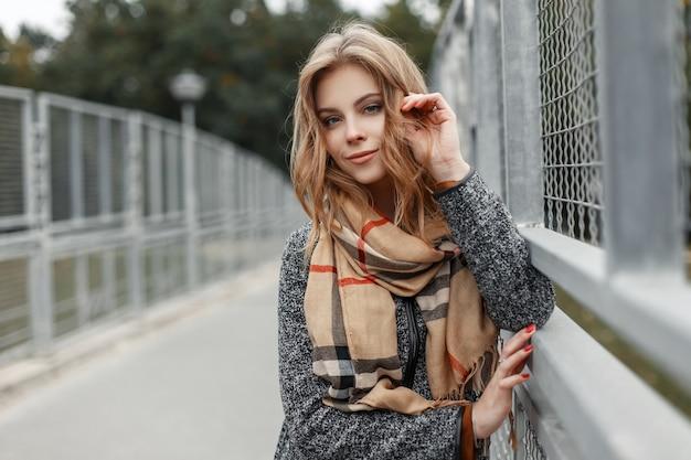 Mooie schattige jonge vrouw met blond haar in een elegante jas met een stijlvolle beige sjaal poseren op een brug in de stad