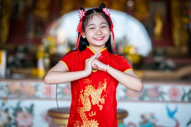 Mooie schattige kleine aziatische jonge vrouw dragen rode traditionele chinese cheongsam, staan voor bidden tot boeddhabeeld voor chinees nieuwjaar festival op chinees heiligdom