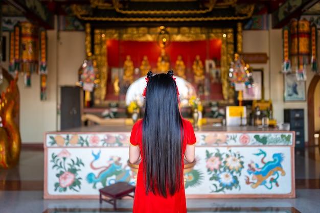 Mooie schattige kleine aziatische jonge vrouw, gekleed in rode traditionele chinese cheongsam