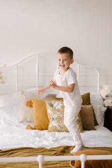 Mooie schattige vierjarige jongen in witte kleren glimlacht en springt op het bed op de lichte achtergrond van het huis