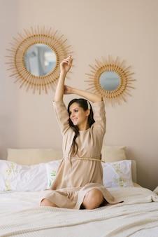 Mooie schattige zwangere vrouw zittend op het bed in beige jurk