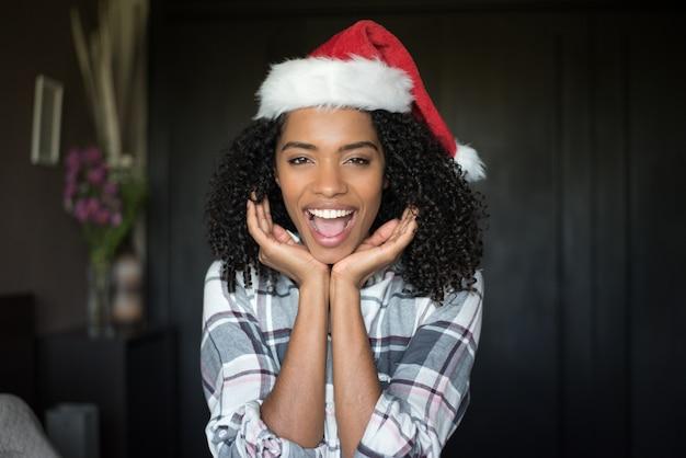 Mooie schattige zwarte jonge vrouw in pyjama op bed met christma
