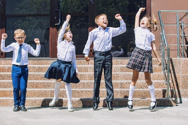 Mooie schoolkinderen actief en gelukkig op de achtergrond van school in uniform