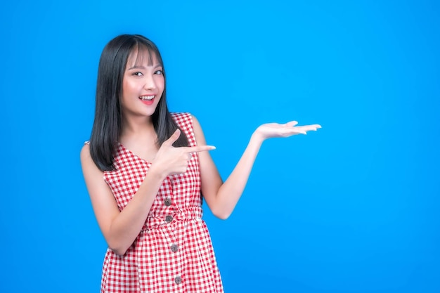 Mooie schoonheid aziatische vrouw schattig meisje met pony kapsel in rode jurk glimlach en poseren haar lege handen met kopie ruimte, lege ruimte voor reclame geïsoleerd op blauwe achtergrond