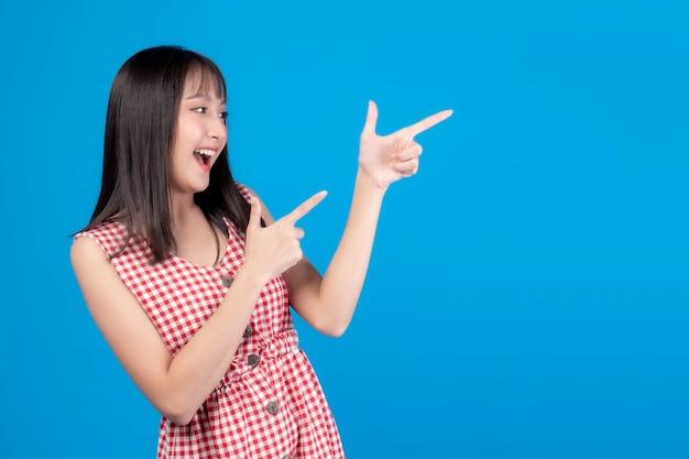 Mooie schoonheid aziatische vrouw schattig meisje met pony kapsel in rode jurk glimlachend en wijzende vinger naar lege kopie ruimte voor elk product aanwezig, lege ruimte voor reclame geïsoleerd op blauwe kleur