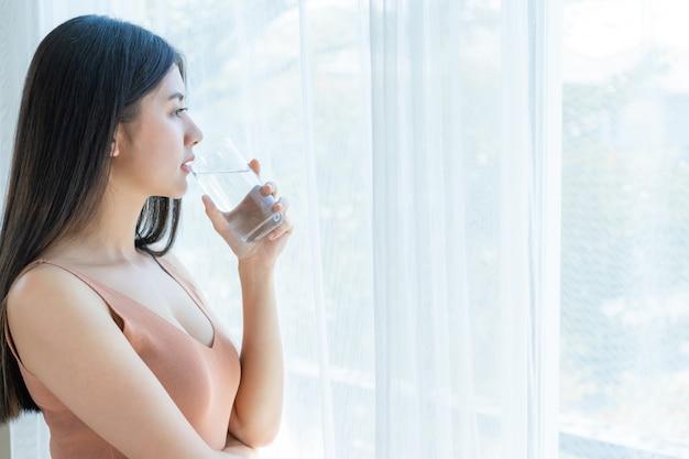 Mooie schoonheid vrouw aziatische schattig meisje voelt gelukkig drinken schoon water drinken voor een goede gezondheid in de ochtend