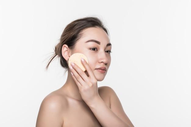 Mooie schoonheids jonge aziatische vrouw die haar gezicht met katoenen stootkussen over wit schoonmaken dat op witte muur wordt geïsoleerd. gezonde huid en cosmetica concept.
