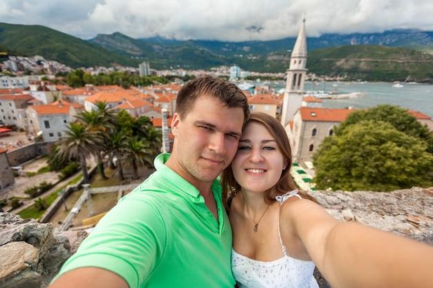 Mooie selfie van een jong verliefd stel poseren tegen de oude stad budva, montenegro