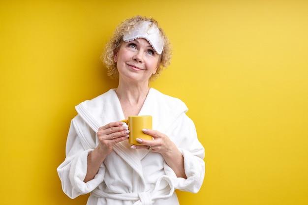 Mooie senior dame elke ochtend begint met een kopje heerlijke koffie, genieten van de tijd alleen, gele mok in handen houden, vóór werkdag of in het weekend