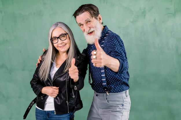 Mooie senior glimlachend vreugdevolle paar, knappe bebaarde man en mooie grijze vrouw, poseren voor camera voor groene muur