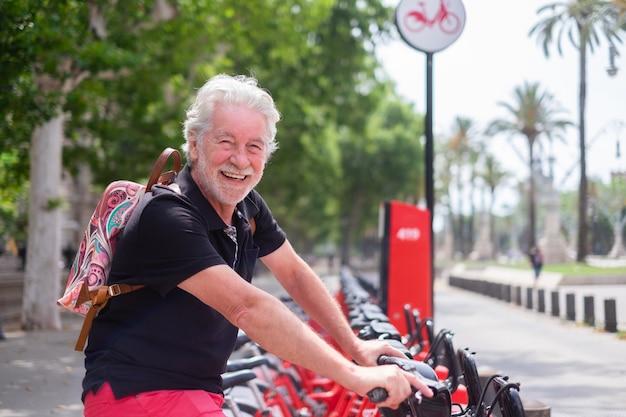 Mooie senior man glimlacht graag een elektrische fiets huren in openbaar park. kaukasisch met baard die naar de camera kijkt en geniet van vrijheid en een gezonde levensstijl