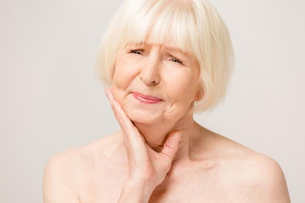 Mooie senior oude vrouw mond met hand aanraken met pijnlijke uitdrukking vanwege kiespijn of tandheelkundige ziekte op tanden. tandarts concept.