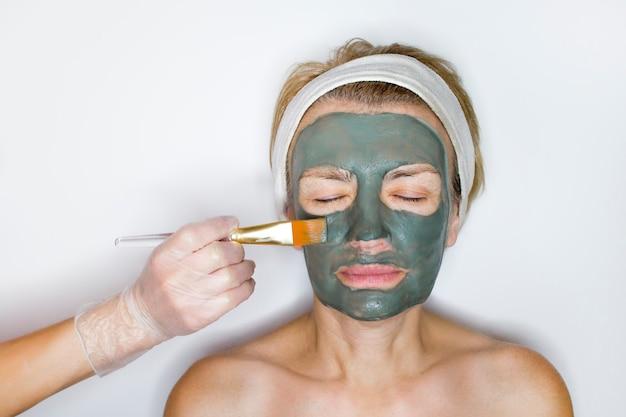 Mooie senior oudere gepensioneerde vrouw doet gezichtsbehandelingen. een blauw kleimasker wordt op het vrouwelijke gezicht aangebracht met een borstel in de hand. lichaamsverzorging, gezicht op oudere leeftijd. persoonlijke verzorging, schoonheid, gezondheid, spa concept