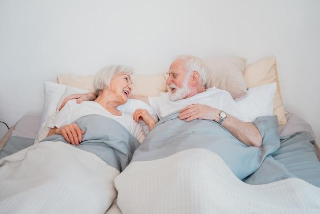 Mooie senior paar genieten van tijd samen thuis - romantische momenten thuis, bejaarde echtpaar in bed thuis