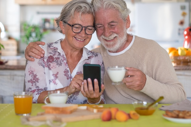 Mooie senior paar ontbijten thuis, samen kijken naar mobiele telefoon. pensioen levensstijl