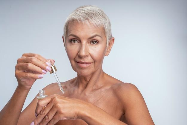 Mooie senior vrouw die lacht terwijl ze serum op de rug van haar hand legt