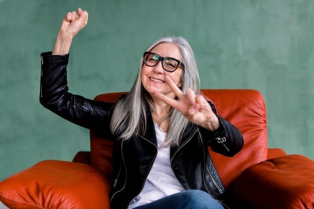 Mooie senior vrouw, gekleed in een bril en stijlvolle trendy leren jas en jeans