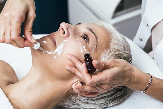 Mooie senior vrouw gezicht tijdens gezichtsbehandeling bij luxe schoonheidskliniek.