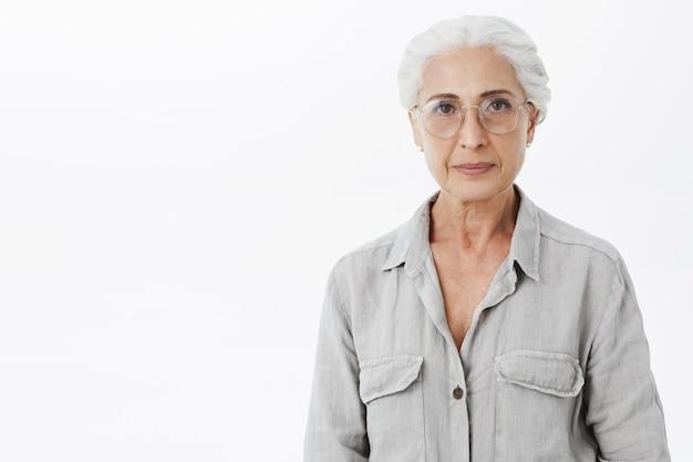 Mooie senior vrouw in glazen glimlachen, witte achtergrond